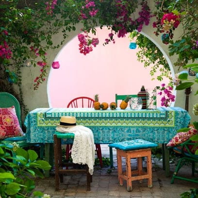 terrasse garten mit Esstisch und Gartenstühlen aus Holz und Tischdecke blau