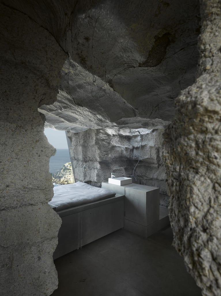 modernes schlafzimmer mit dusche aus sichtbeton und matratze vor dem panoramafenster