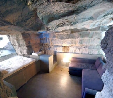 kleines Wohn schlafzimmer aus beton mit ecksofa blau und dusche