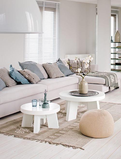 holzboden für weiße Wohnzimmergestaltung mit teppich beige und sofadekoration mit Hellblauen kissen