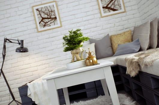 modernes wohnzimmer mit weißen ziegelwänden und DIY ecksofa grau aus Paletten mit couchtisch holz mit Bonsai