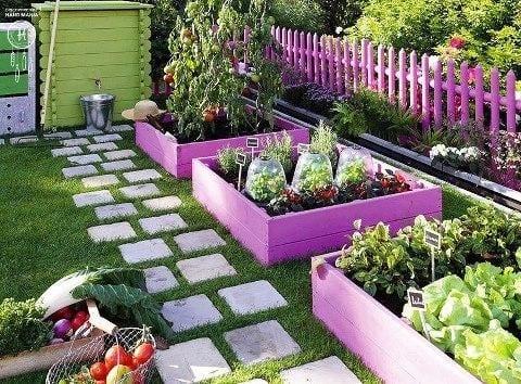 farbige gartengestaltung mit gartenzaun und pflanzenbetten in lila
