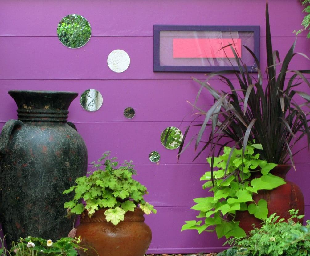 lila gartenwand mit runden spiegeln dekoriert