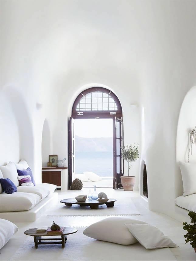 einfache und elegante Inneneinrichtung in weiß mit weißen sitzkissen und kamin