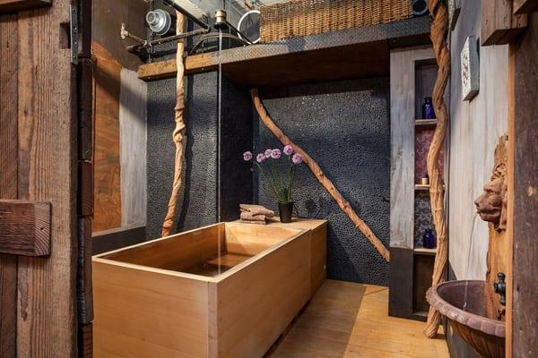 rustikales badezimmer mit schwarzer wand und löwenkopfbrunen