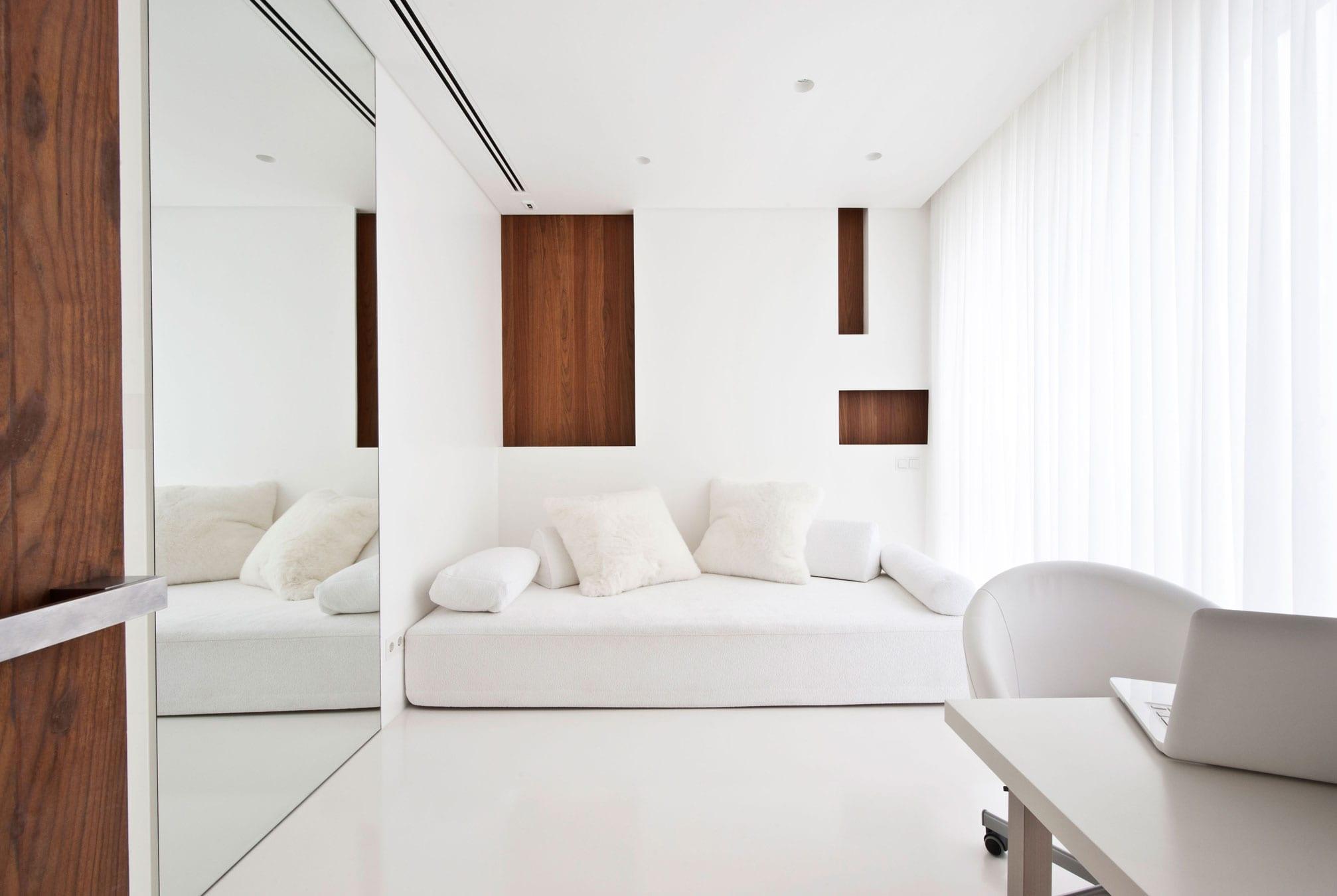 minimalistische Zimmergestaltung in weiß mit polstersofa weiß und bürotisch mit bürostühl weiß