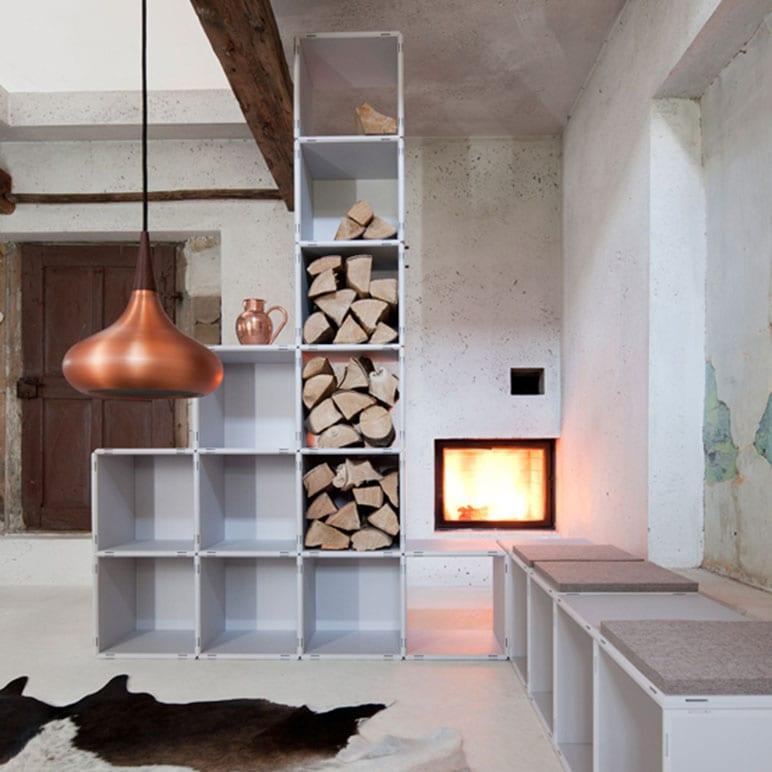 modernes wohnzimmer design mit kamin und weißem modularem regalsystem