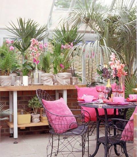 Palmengarten und schwarzen Gartenmöbel aus Stahl mit rosafarbigen Kissen