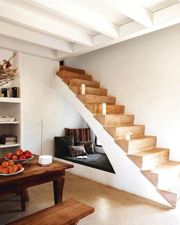 kleines wohnzimmer interior mit sitzecke unter Innentreppe mit holzstuffen und Esstisch massiv