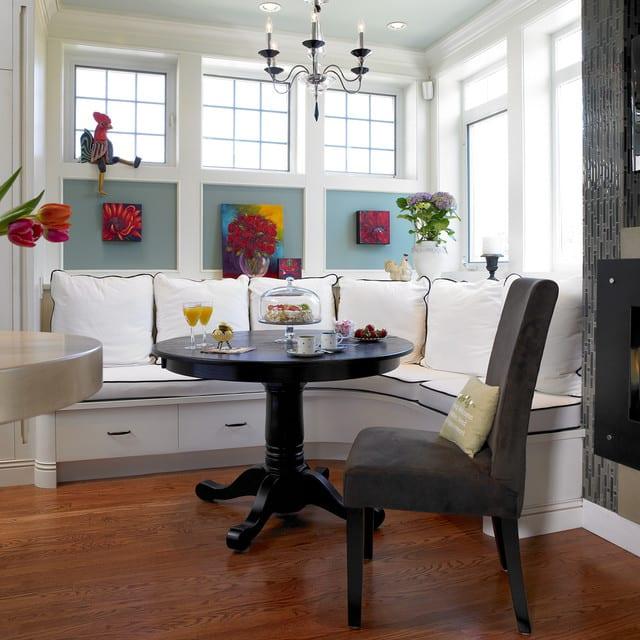moderne küchenwandgestaltung mit blumenbildern an blauer wand und kleine runde sitzecke küche in weiß