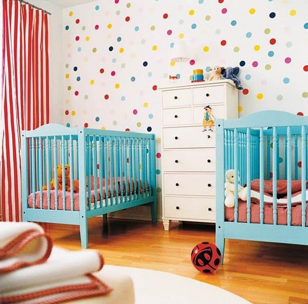 babyzimmer tapete mit punkten als hintergrund für blaues gitterbett und sideboard weiß