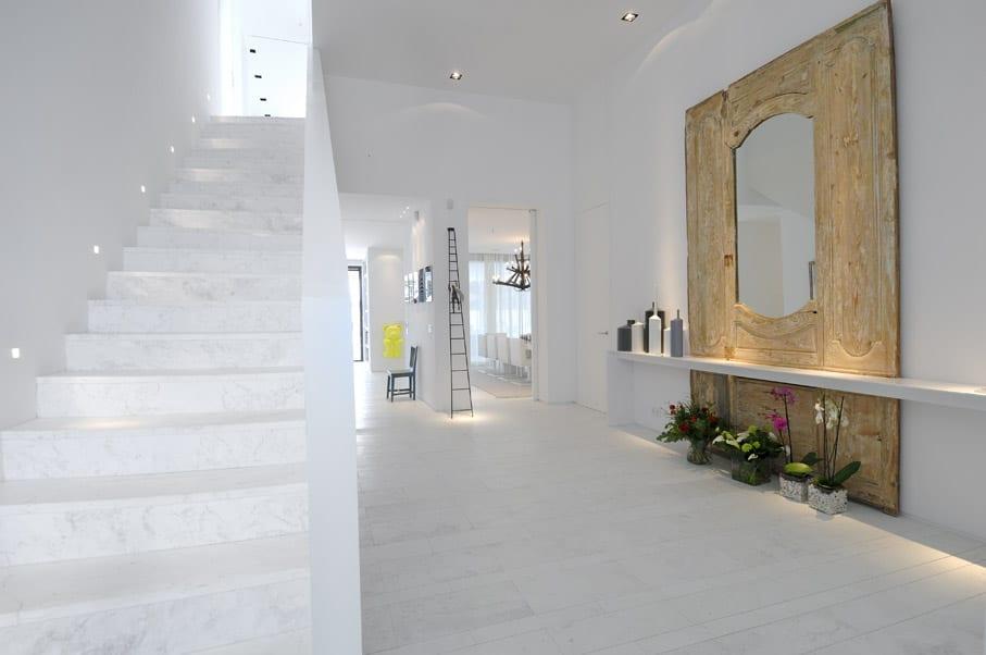 weiße Innentreppe aus Marmor und Flurgestaltung mit rustikaler Wanddekoration aus Holz und hängesideboard