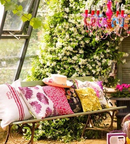 frische gartengestaltung mit kletterblumen und rustikaler gartenbank aus holz und stahl
