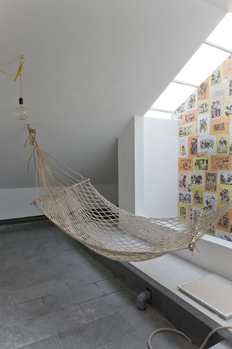 wohnzimmer mit dachschräge und hängematte als minimalistisches Interior design