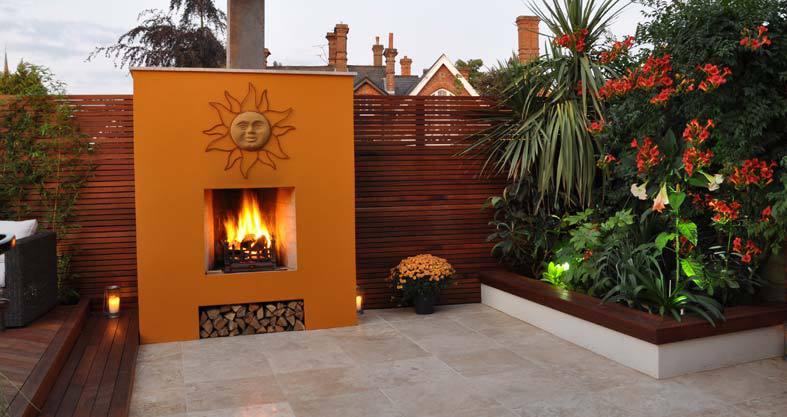 traumgarten mit gartenzaun aus holz als sichtschutz garten und außenkamin mit wandfarbe orange als gartendeko