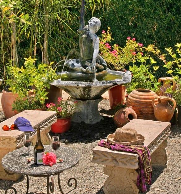 gartengestaltung mit gartenbrunnen und schicke steingartenbänken