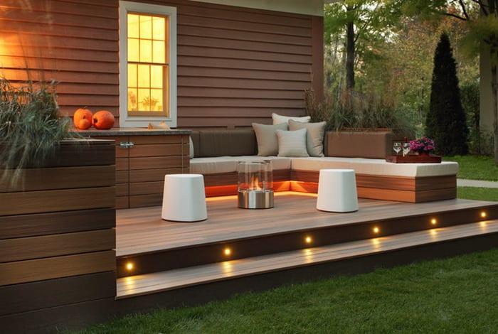 holzterrasse mit Sitzecke und gartenbeleuchtung als Gartengestaltung