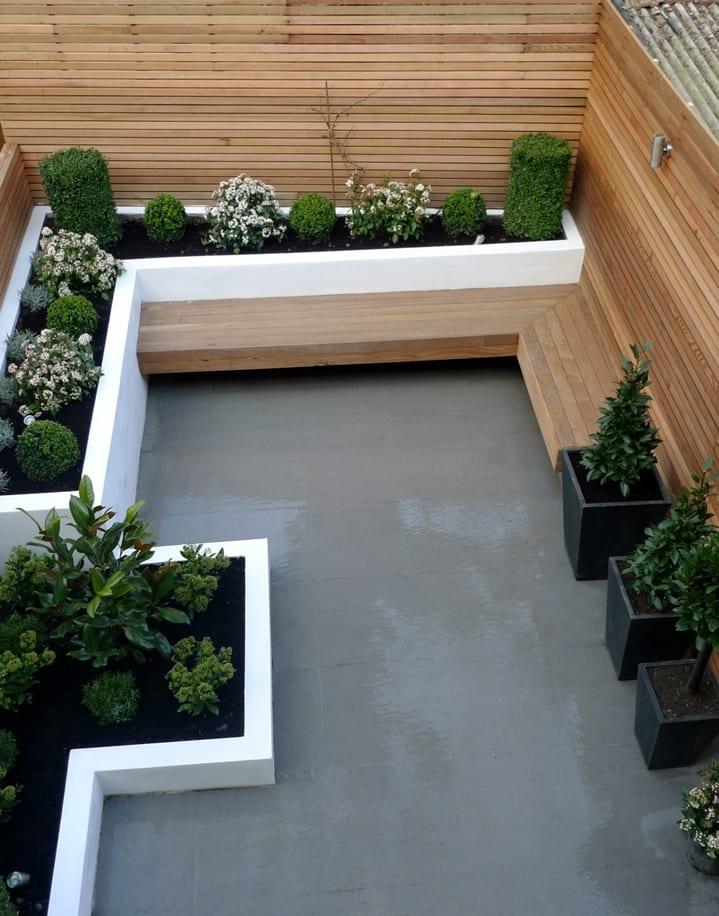 traumgarten mit ausgemauerten pflanzenbeeten weiß und sitzecke aaus holz