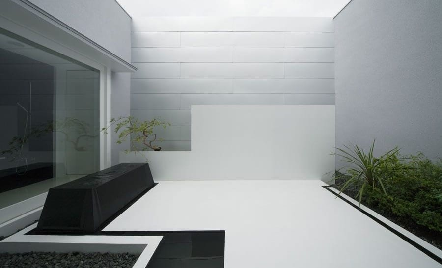 moderner terrasse garten in weiß mit gartenbank und kies