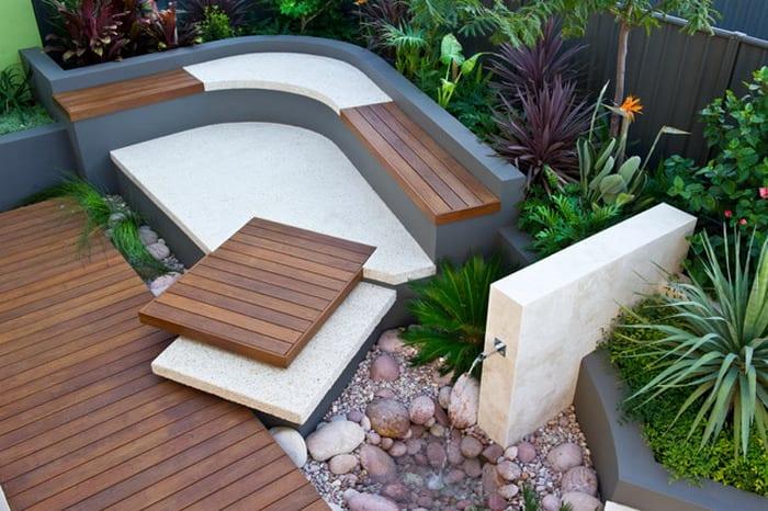 gartengestaltung mit terrassendiele und Gartenbank gerundet in weiß und grau