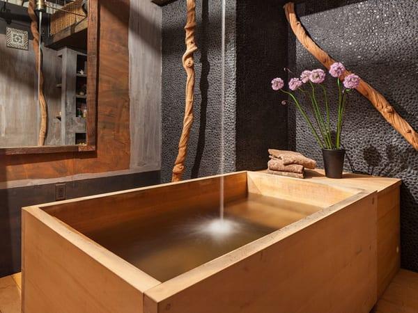 badezimmer einrichtung mit freistehender badewanne aus holz und kreative badezimmer wnadgestaltung mit schwarzen steinchen