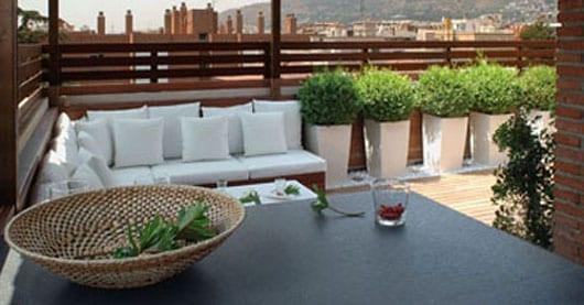 gartenbank mit weißen Sitzkissen als terrassengestaltung mit sichtschutz
