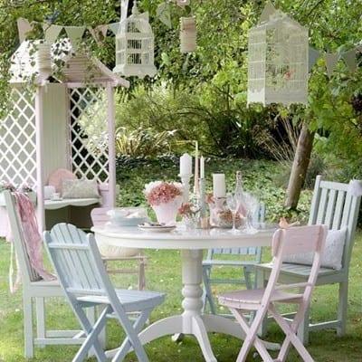 runder esstisch weiß mit weißen Holtstühlen und hängenden Vogelkäfigen