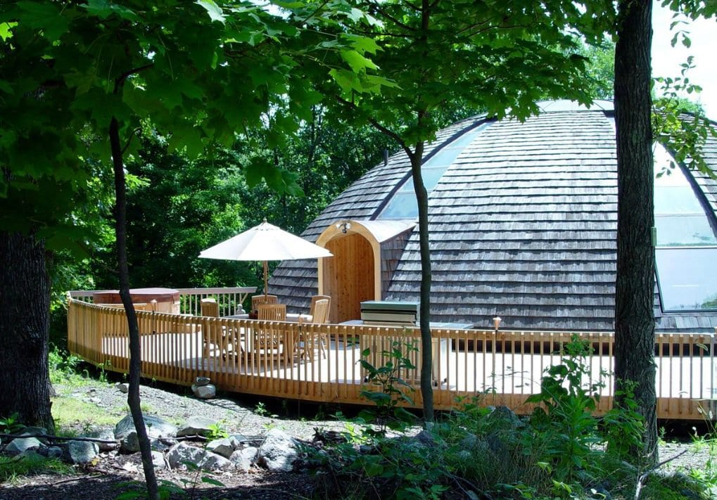luxus haus mit gerundeter Holzterrasse als Ökohaus mit Solarpaneelen