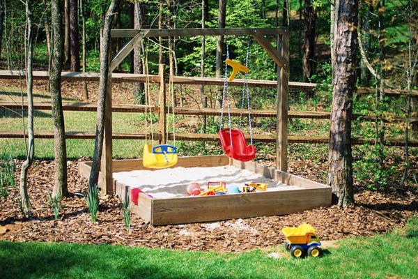 Kinderspielplatz mit schaukel und sandkasten als SPielplatz im wald
