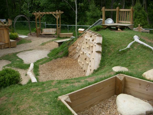 kinderspielplatz mit rutsche und kletterwand aus holz zum spielen im freien