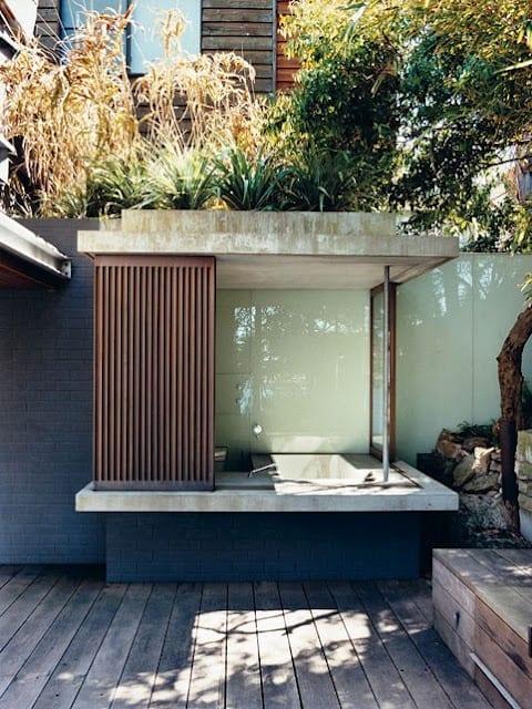 gartengestaltung mit Holzterrasse und Gartenmauer aus schwarzen ziegeln und überdachte badewanne eingemauert und verkleidet mit ziegeln