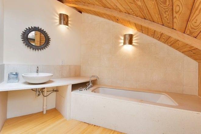 kleines badezimmer mit badewanne verkleidung aus naturstein weiß und gewölbter holzdecke