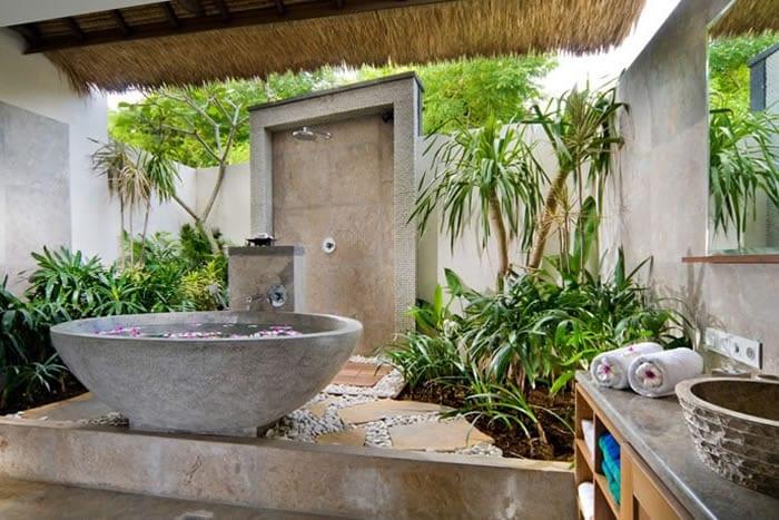 badezimmer im hofgarten mit badewanne aus naturstein und Duschwand