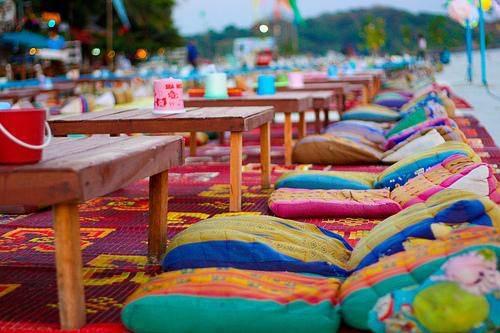 teppich in pink mit farbigen kissen und couchtische aus holz für gartenparty