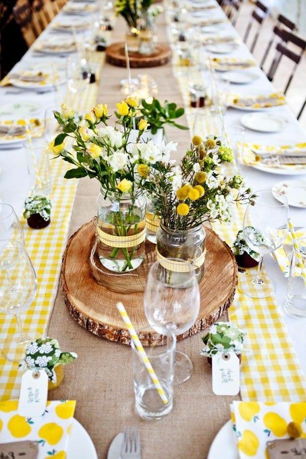 tischdeko in gelb mit runden Holzgestellen und Blumen in weiß und gelb