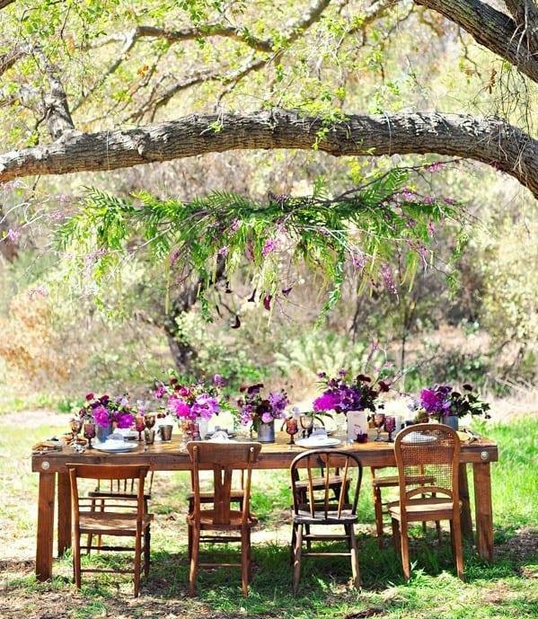 gartenparty deko mit lila blumen als tischdeko und hängende party deko aus zweigen