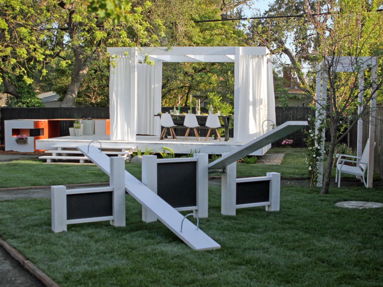 moderne gartengestaltung mit Holzterrasse weiß und Kinderspielgeräte aus holz