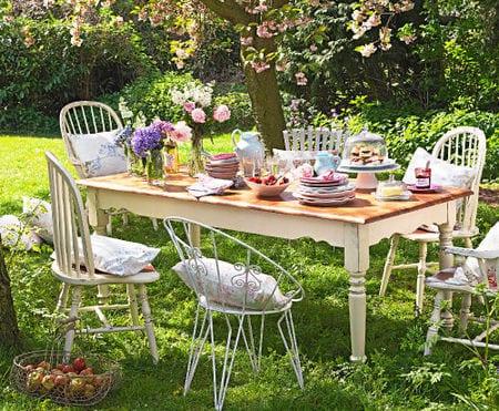 Holzesstisch mit rustikalen holzstühlen für Gartenparty im Frühling