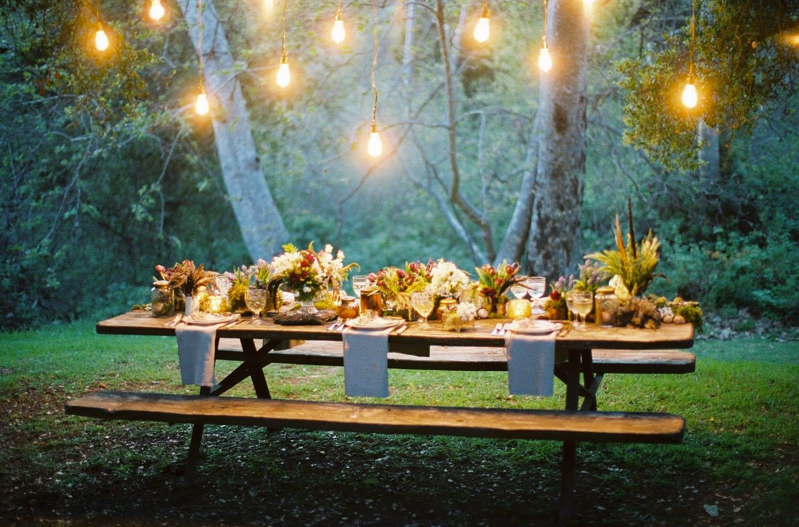 einfache dekoration für sommerparty im garten mit Holzesstisch und gartenbänken