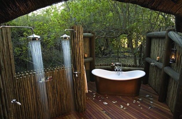 holzterrasse mit Sichtschutzwand aus Rundhölzern als offenes Badezimmer einrichten