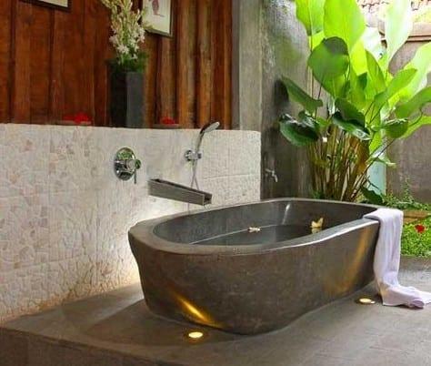 freistehende badewanne aus naturstein grau für offenes badezimmer im garten