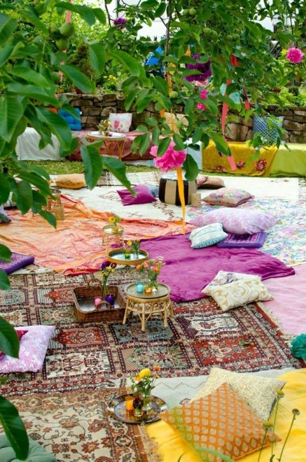 gartendeko mit teppichen und kissen für gartenparty am boden