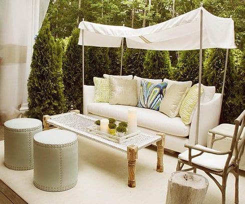 moderne gartengestaltung in weiß mit couchtisch holz und runden lederhockern und Sofa mit Sonnenschutz