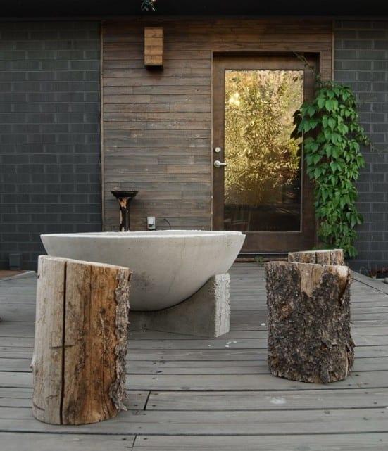 Holzterrasse gestalten mit freistehnder badewanne aus beton und Holzhockern