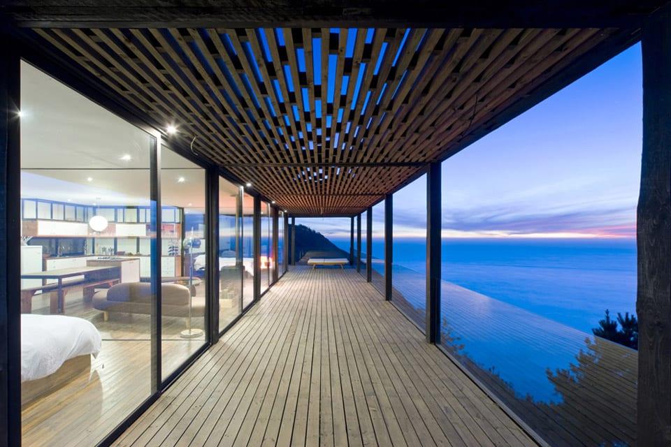 Traumhaus mit moderner Einrichtung und Holzüberdachung mit Holzstützen und Glasgeländer
