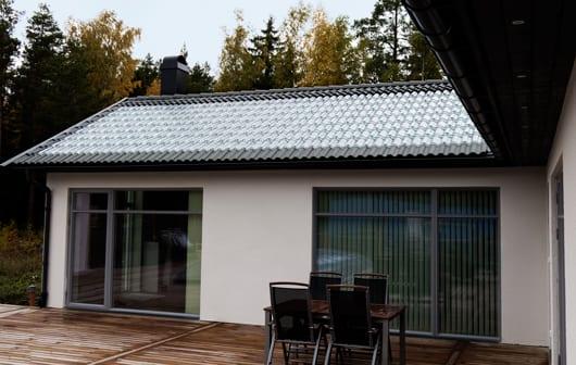 modernes Haus mit Glasdachziegeln als Deckung von Solaranlage