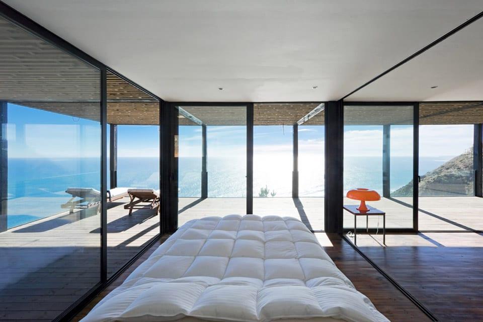 luxus Schlafzimmer mit Holzboden und große Terrasse mit Blick aufs meer