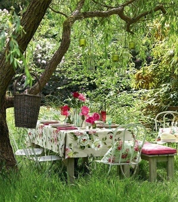 tischdecke mit rosenmuster und grünen teelichthalter aus glas für gartenparty deko