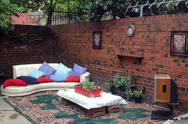 coole gartengestaltung mit teppich und sofa weiß als offenes wohnzimmer und gartenmauer deko ideen
