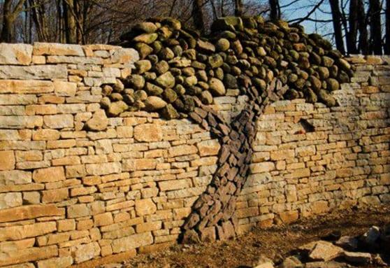 gartengestaltung mit Trockenmauer und mauerdeko mit einem Baumbild aus runden Steinen